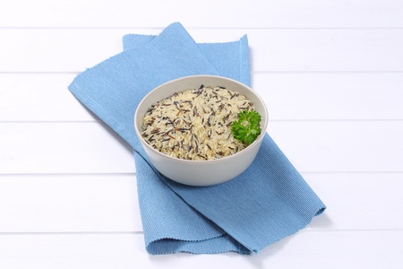 bowl of wild rice on blue place mat Stock Photo