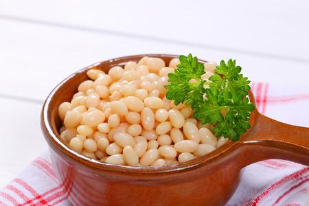 통조림 된 흰 콩의 냄비 체크 무늬 dishtowel에 - 가까이
