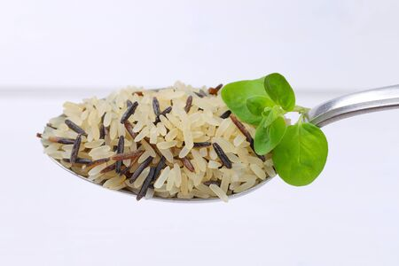 spoon of wild rice on white wooden background