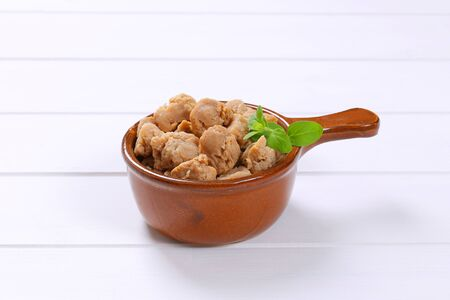 saucepan of soy meat cubes on white wooden background