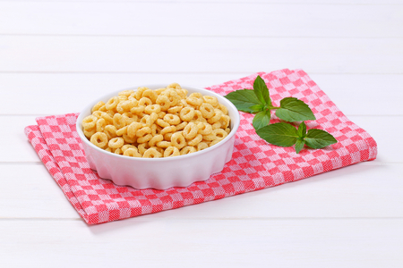 bowl of honey cereal rings on checkered place mat Stock Photo