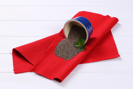 bowl of chia seeds spilt out on red place mat Stock Photo