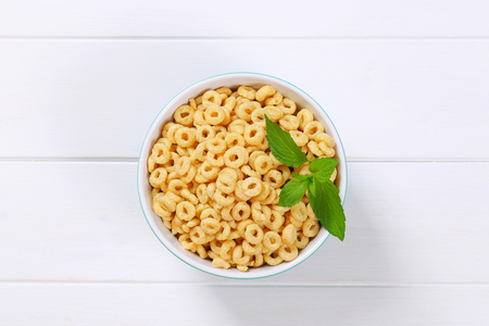 bowl of honey cereal rings on white wooden background