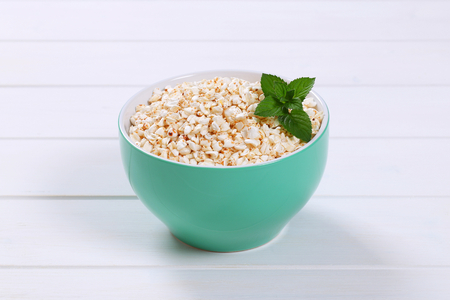 bowl of puffed buckwheat on white wooden background