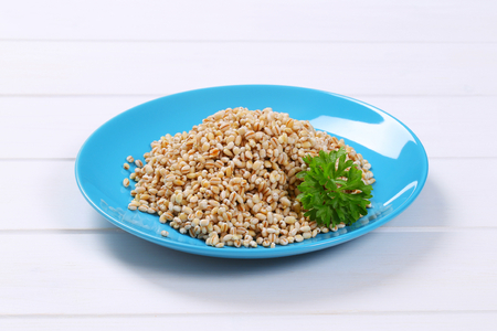 plate of cooked pearl barley on white wooden background