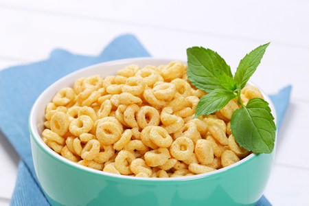 bowl of honey cereal rings on blue place mat - close up