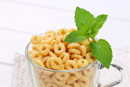 cup of honey cereal rings on white table mat - close up