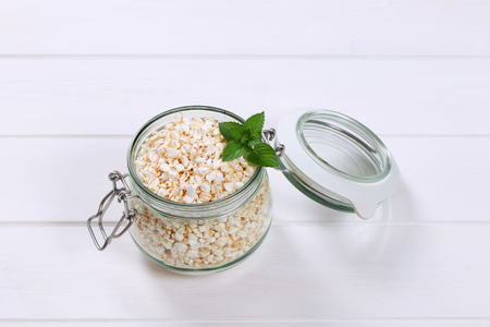 jar of puffed buckwheat on white wooden background Stock Photo