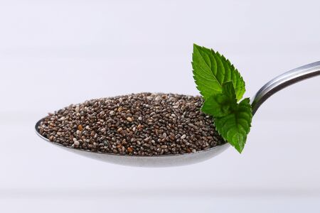 spoon of chia seeds on white wooden background
