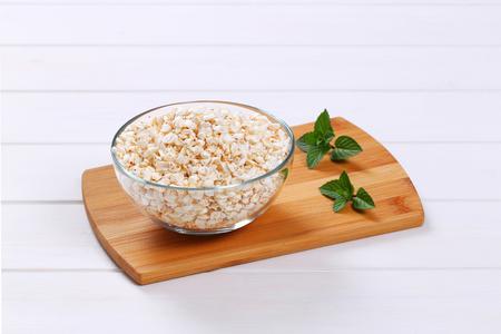 bowl of puffed buckwheat on wooden cutting board