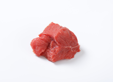 small piece of raw beef meat on white background