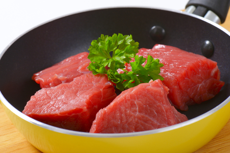 close up of diced raw beef meat with parsley in frying pan Reklamní fotografie