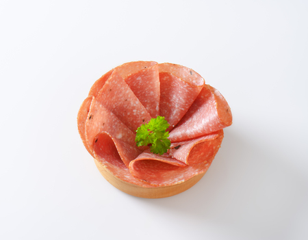 thin slices of spicy salami folded on white background