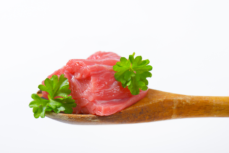 piece of raw beef meat with parsley on wooden spoon - close up