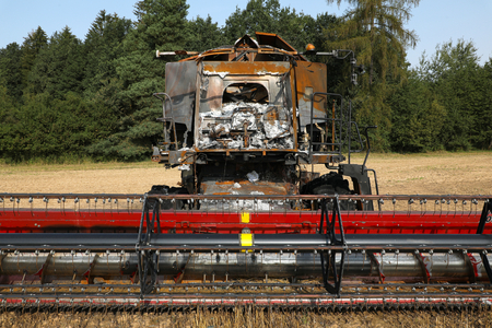 Burnt out combine harvester in field - front view Banco de Imagens