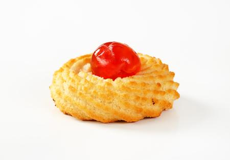 Tradiční sicilské mandle cookie nahoře s glace třešeň na bílém pozadí