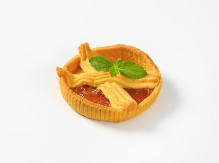 small apricot jam tart on white background