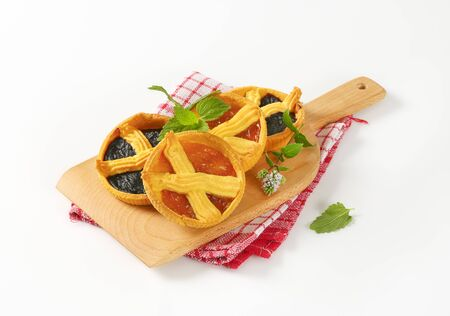 apricot and plum jam tarts on wooden cutting board