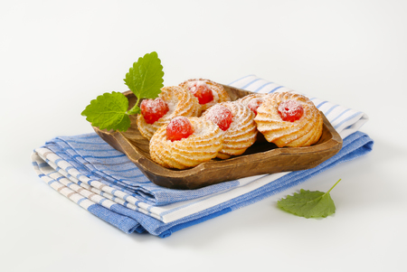 Traditional Sicilian almond cookies topped with glace cherries and sprinkled with powdered sugar