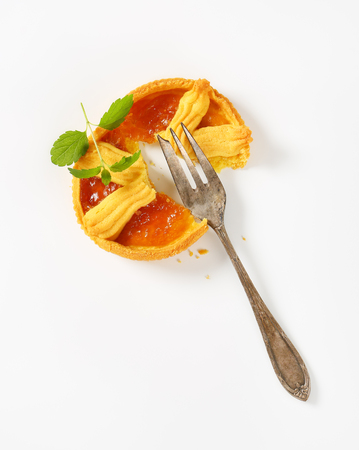 halved apricot jam tart and silver fork on white background