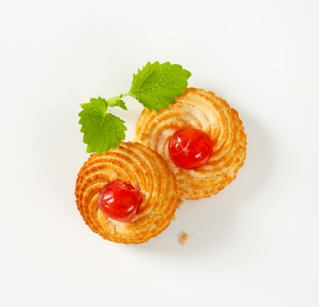 Traditional Sicilian almond cookies topped with glace cherries on white background