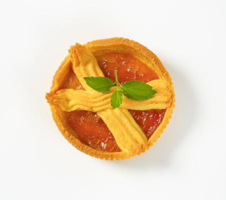 small apricot jam tart on white background