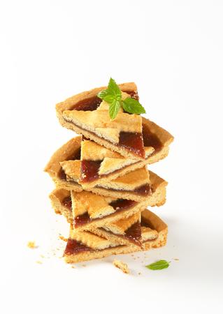 stack of strawberry jam tart slices on white background