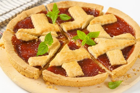 close up of sliced strawberry jam tart with lattice on top
