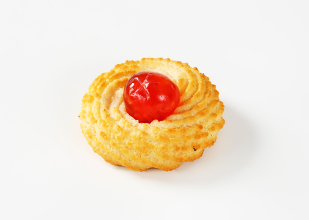Traditional Sicilian almond cookie topped with glace cherry on white background