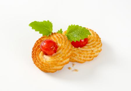 Tradiční sicilské mandlové sušenky doplněné glace třešně na bílém pozadí