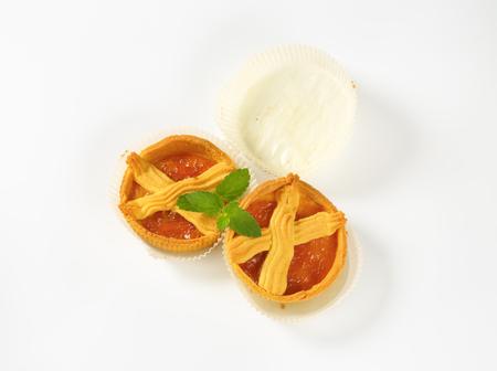 small apricot jam tarts on white background