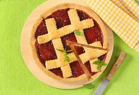 strawberry jam tart with lattice on top on wooden cutting board
