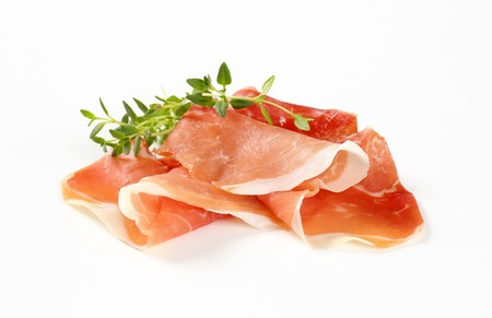 slices of air dried ham with thyme on white background Reklamní fotografie