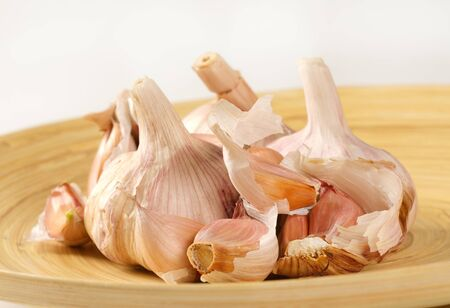 bulbs and cloves of fresh garlic on wooden plate - close up