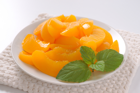 plate of peeled and sliced peaches on white table mat - close up Stok Fotoğraf