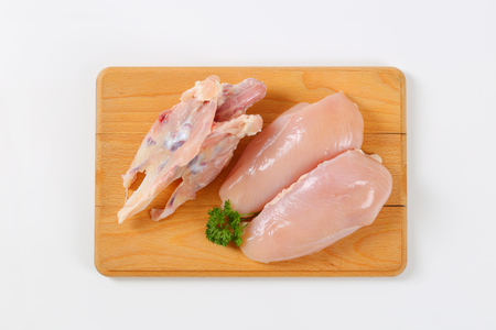 raw turkey breasts and chest on wooden cutting board Stock Photo