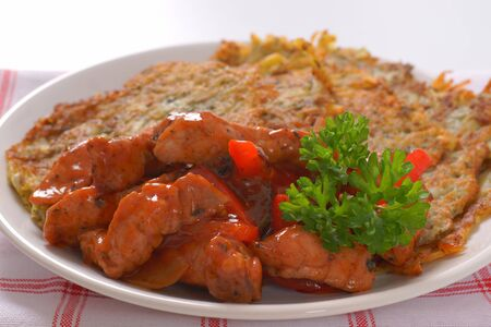 plate of potato pancakes with spicy chicken stir fry Stock Photo