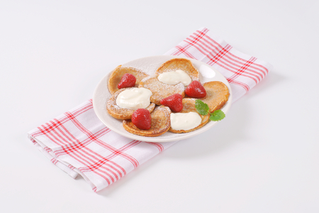 plate of small pancakes with whipped cream and strawberries