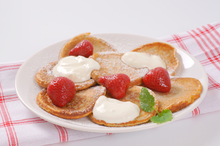 plate of small pancakes with whipped cream and strawberries - close up