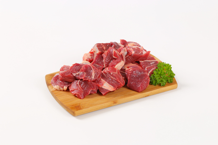 diced raw beef meat on wooden cutting board