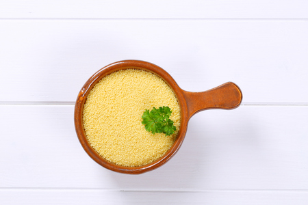 saucepan of raw couscous on white wooden background Archivio Fotografico