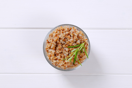 glass of cooked buckwheat on white wooden background Stok Fotoğraf