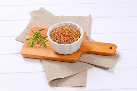 bowl of raw buckwheat on wooden cutting board