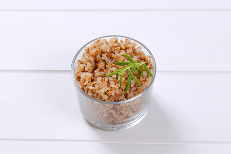 glass of cooked buckwheat on white wooden background Stock Photo