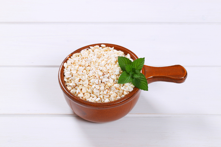 saucepan of puffed buckwheat on white wooden background Stock Photo