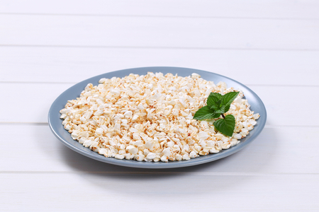 plate of puffed buckwheat on white wooden background Stock Photo