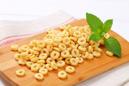 pile of honey cereal rings on wooden cutting board - close up Stock Photo