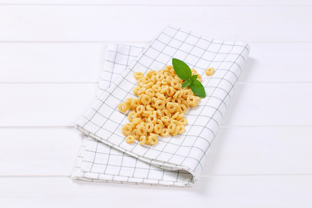 pile of honey cereal rings on checkered dishtowel