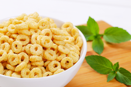 bowl of honey cereal rings on wooden cutting board - close up