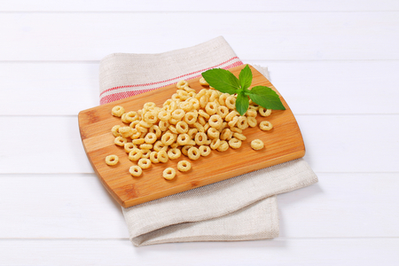 pile of honey cereal rings on wooden cutting board